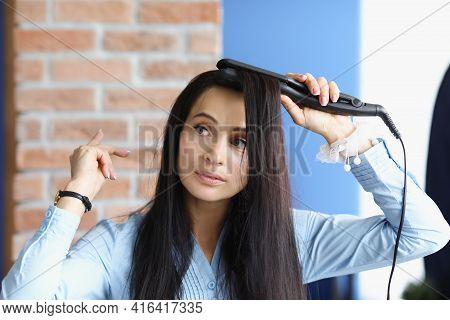 Brunette Woman Does Curling Of Her Hair With Curling Iron