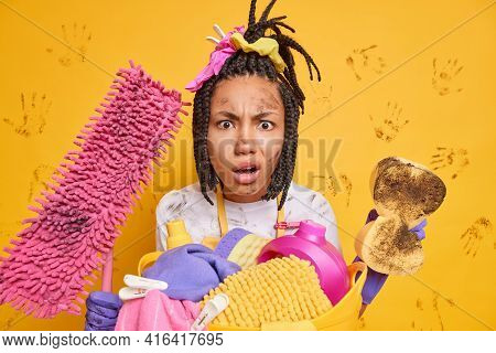 Puzzled Displeased Young Afro American Woman With Combed Dreadlocks Holds Dirty Sponge And Mop Busy