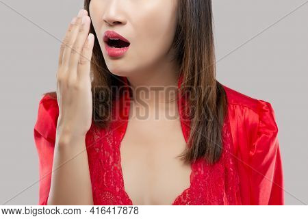 Thailand Woman Doing A Hand Breath Test At Night. Asian Women In Red Satin Nightwear Have Bad Breath
