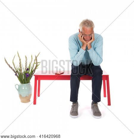 Senior man with mobile phone in waiting room