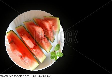 Juicy Ripe Watermelon Is Cut On Cubes And Laid Out On A White Plate. In Pieces Of Watermelon Color S