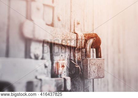 On The Gray Old Wooden Gate Is A Rusty Latch, On Which Hangs An Old Metal Lock, Illuminated By Sunli