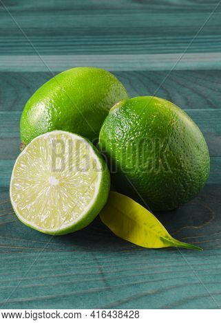 Green Limes And Half A Lime On A Green Wooden Background Vertical