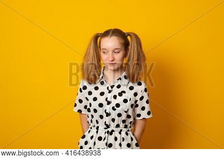 Shy Child Girl With Two Ponytails On A Yellow Background. Teenage Girl Is Shy About Her Hairstyle.