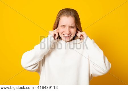 Displeased Teen Girl Plugs Ears With Discontent, Doesnt Want To Hear Annoying Sound Or Noise, Dresse