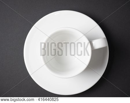 White Coffee Cup And Saucer Made Of Porcelain On A Black Background. Top View, Flat Lay