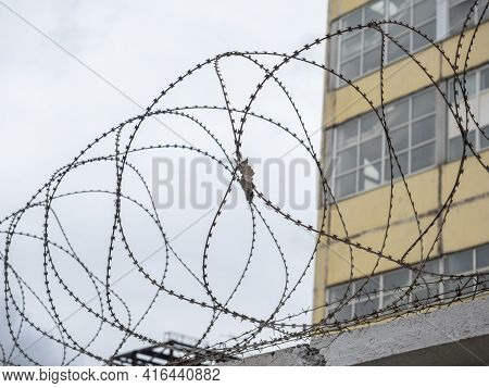 Close-up Of The Barbed Wire On The Fence. Building In The Background. The Concept Of Protecting Bord