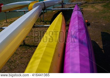 On The Banks Of The River Lie A Multi-colored Canoe Close-up