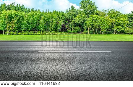 Side View Of Asphalt Straight Street Roadway Of Lanes With Lines And Green Trees With Blue Sky In Ba