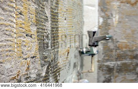 Selective Focus. Old Grungy Concrete Wall With Defocusing Shower Faucet  As Background Or Texture. B