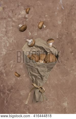 Flying Food. Flying Mushrooms Champignons In Paper Packaging On A Beige Background. Royal Brown Mush
