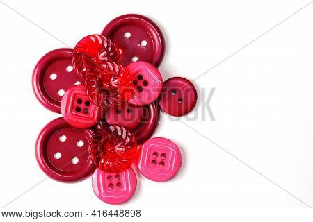 Colorful Red And Pink Buttons On A White Background. Lots Of Red Buttons. Old Vintage Buttons Close