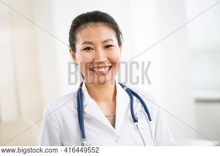 Portrait of smiling young asian female doctor in a background for your text.