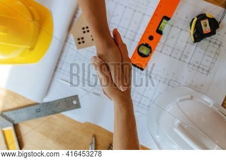 Top View Of Engineer, Architect, Construction Worker Team Hands Shaking After Plan Project Contract