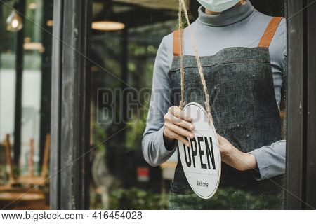 Open. Waitress Staff Wearing Protection Face Mask, Apron Turning Open Sign Board On Glass Door In Mo
