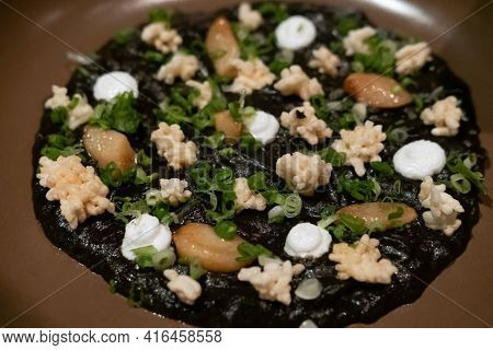 Delicious Italian Risotto With Cuttlefish Ink Or Squid-ink With Cauliflower. Black Risotto. Healthy