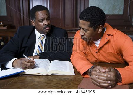 Middle aged advocate sitting with criminal in the courtroom