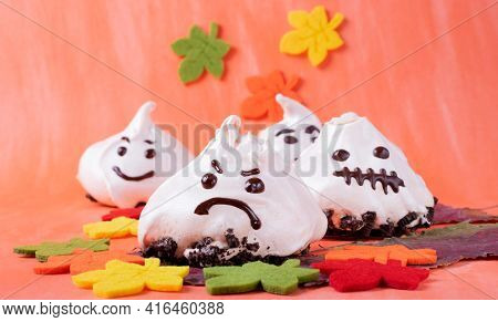 Funny Meringue Ghosts With Funny Faces Against The Orange Background. Halloween Dessert
