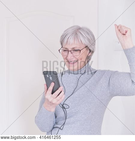 A Gray-haired Senior Woman With Glasses, In Headphones, In A Gray Turtleneck Looking At The Smartpho