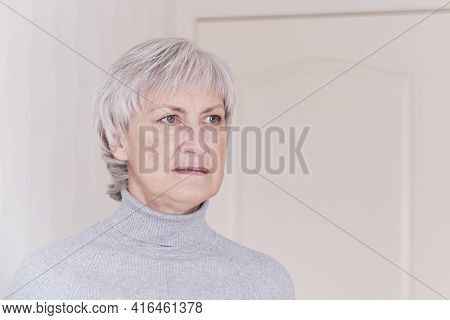 A Close-up Portrait Of A Worried About Something Older Caucasian Woman With Short Gray Hair In A Gra