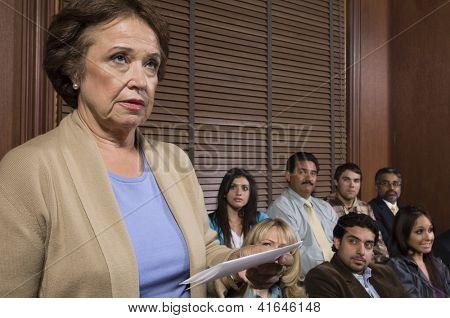 Abogado Senior en pie con papel en la sala de audiencias y la gente en el fondo