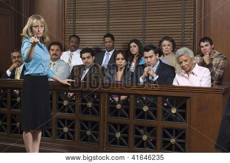Retrato de un defensor mujer apuntando con jurados sentados juntos en el estrado en el Tribunal ho
