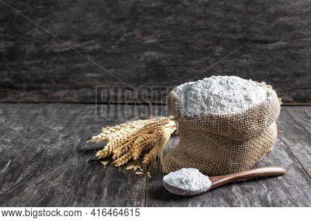 Multigrain  Flour In Small Burlap Bag On Rustic Wooden Table