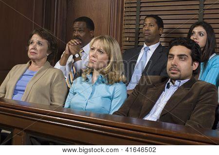 Grupo de empresarios sentados juntos en el estrado del Palacio de justicia