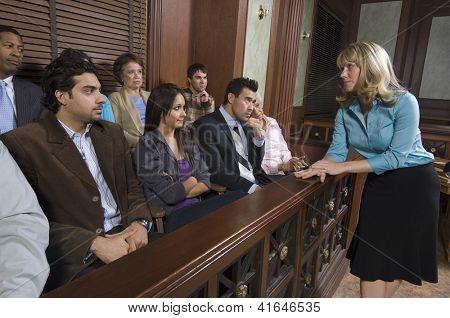 Defensor mujer hablando con los miembros del jurado sentado en el estrado en el Palacio de justicia