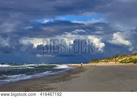 Blue Dramatic Clouds And Sunbeams Break Through Over The Beach