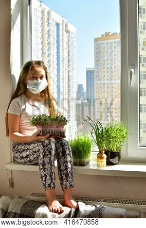 European Girl In Protective Mask Watering The Plants On The Windowsill,takes Care Of The Plants.quar