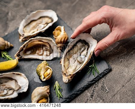 Woman hand holding fresh oyster taken from black platter with cooked snails, seafood and lemon