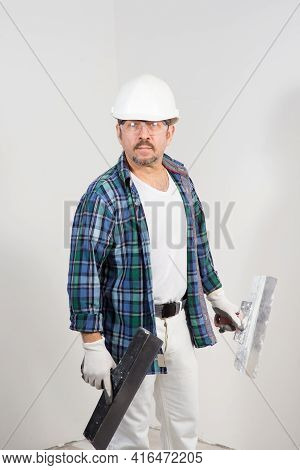 A Construction Worker In A Protective Helmet With A Putty Knife On A White Wall Background