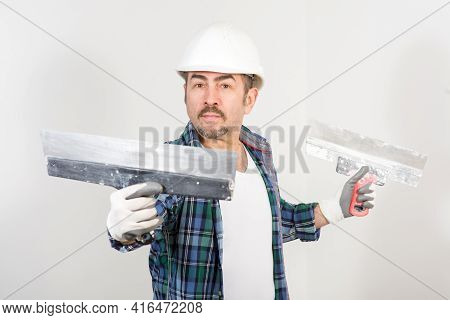 Builder In Safety Helmet With Two Putty Knifes On White Wall Background