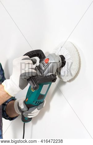 Construction Worker Repairman In Safety Helmet With Wall Sander Close-up