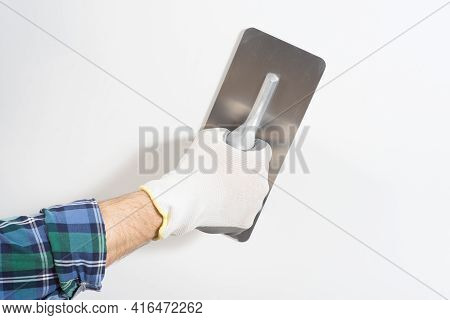 Builder In Safety Helmet Plastering White Wall With Decorative Filler Knife Close-up
