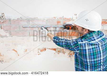 Builder Repairman Measures The Length Of A Plastered Brick Wall With A Construction Tape During The