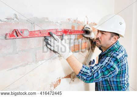 A Builder In A Safety Helmet Checks A Flat Brick Wall With A Building Level While Repairing A House,