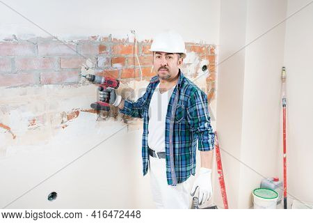 A Builder-repairman In A Protective Helmet Holds An Electric Screwdriver In His Hand During The Repa