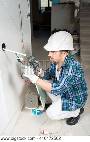 An Electrician Builder In A Protective Helmet Measures The Voltage With A Voltmeter Of An Electrical
