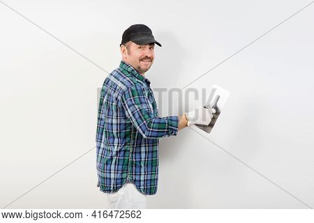 A Builder In A Black Cap Plastering A White Wall With A Knife For Decorative Plaster, Putty
