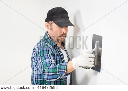 Builder In Black Hat Plastering A White Wall With A Knife For Decorative Plaster, Putty When Renovat
