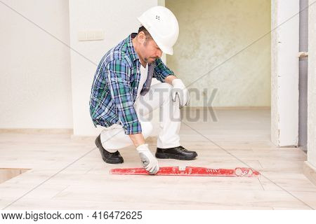 A Builder In A Protective Helmet Checks The Flatness Of The Tiles On The Floor During Repairs, Build