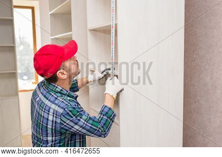 Furniture Assembler Measures Cabinet Height With Construction Tape During Assembly, Close-up