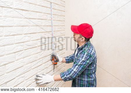 A Construction Worker Measures The Height Of A Decorative Brick Wall With A Construction Tape.