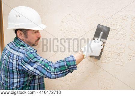 Builder Repairman Plasterer, In A Protective Helmet, During The Repair Applies Decorative Plaster, P