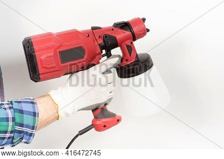 A Builder Paints A Wall With An Electric Spray Gun, A Close-up, During A House Renovation, Renovatio