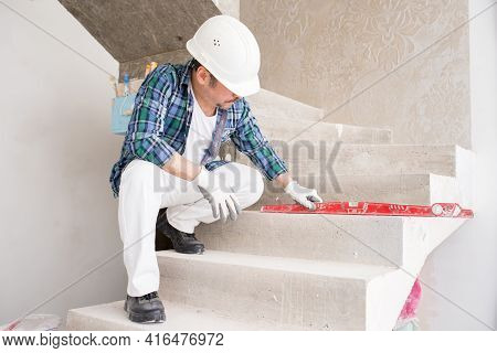 A Builder-repairman, Foreman, In A Protective Helmet, Checks The Evenness Of A Concrete Structure, S