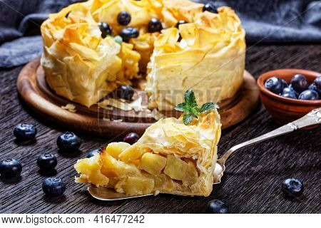 Close-up Of Layered Apple Blueberry Pie With Phyllo Crust On A Dark Rustic Wooden Table, Horizontal