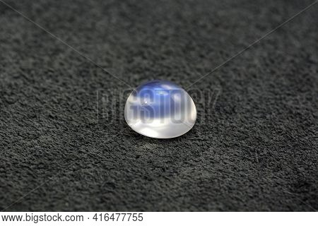 Natural Adularia Blue Sheen Oval Cabochon Moonstone. Loose Gem On Gray Textured Real Leather Backgro